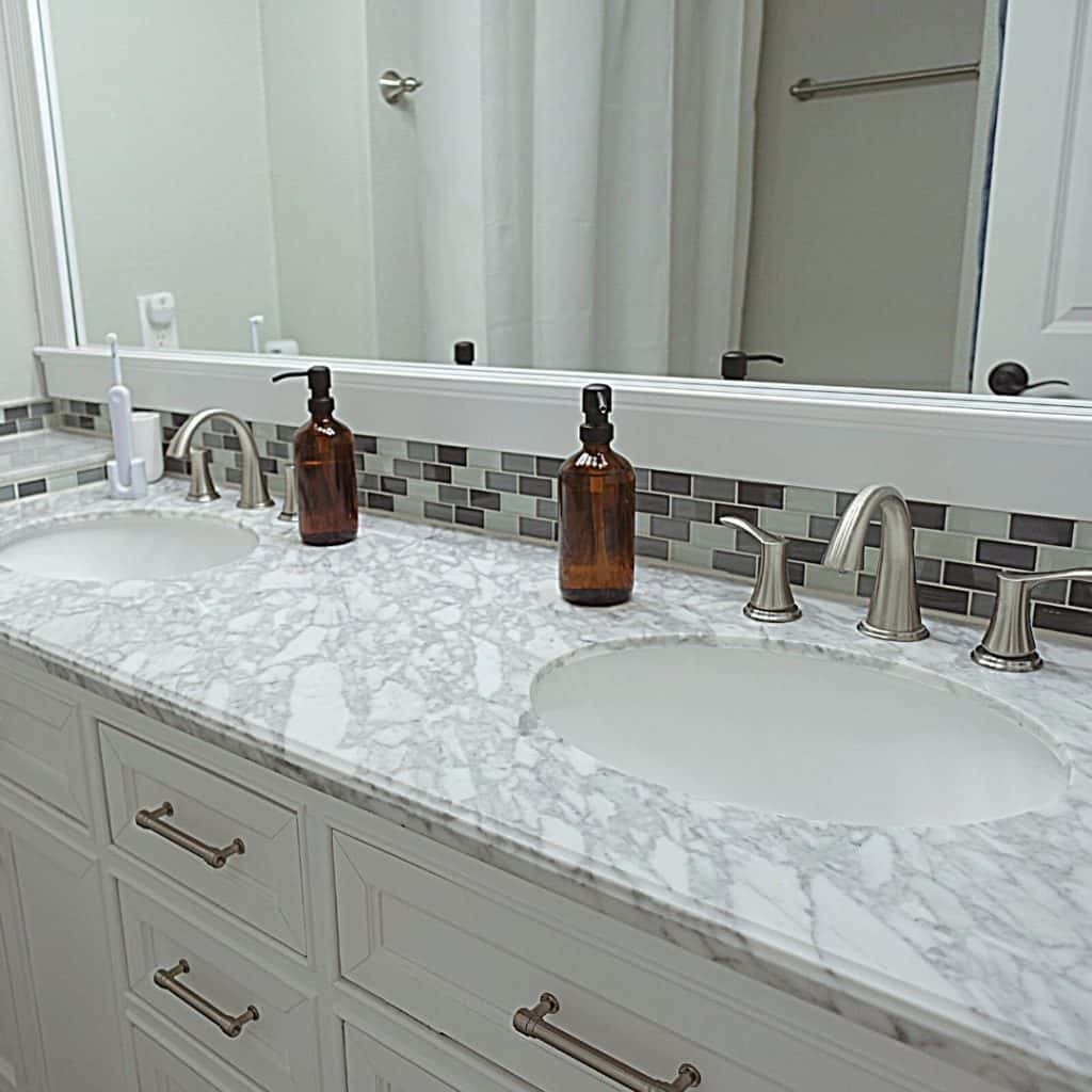 decluttering tips for hoarders bathroom with grey granite and subway tile and amber soap jars