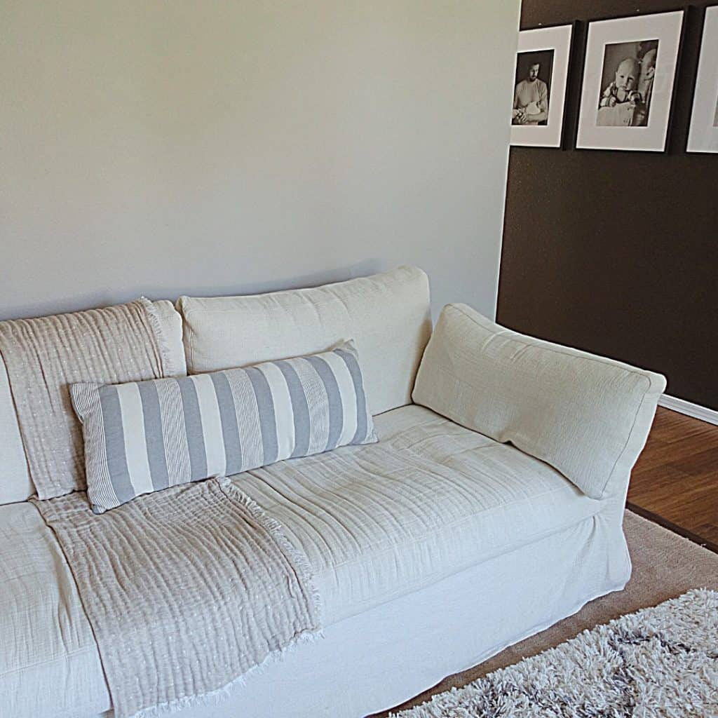 decluttering tips for hoarders image of cream color slip covered couch with black wall