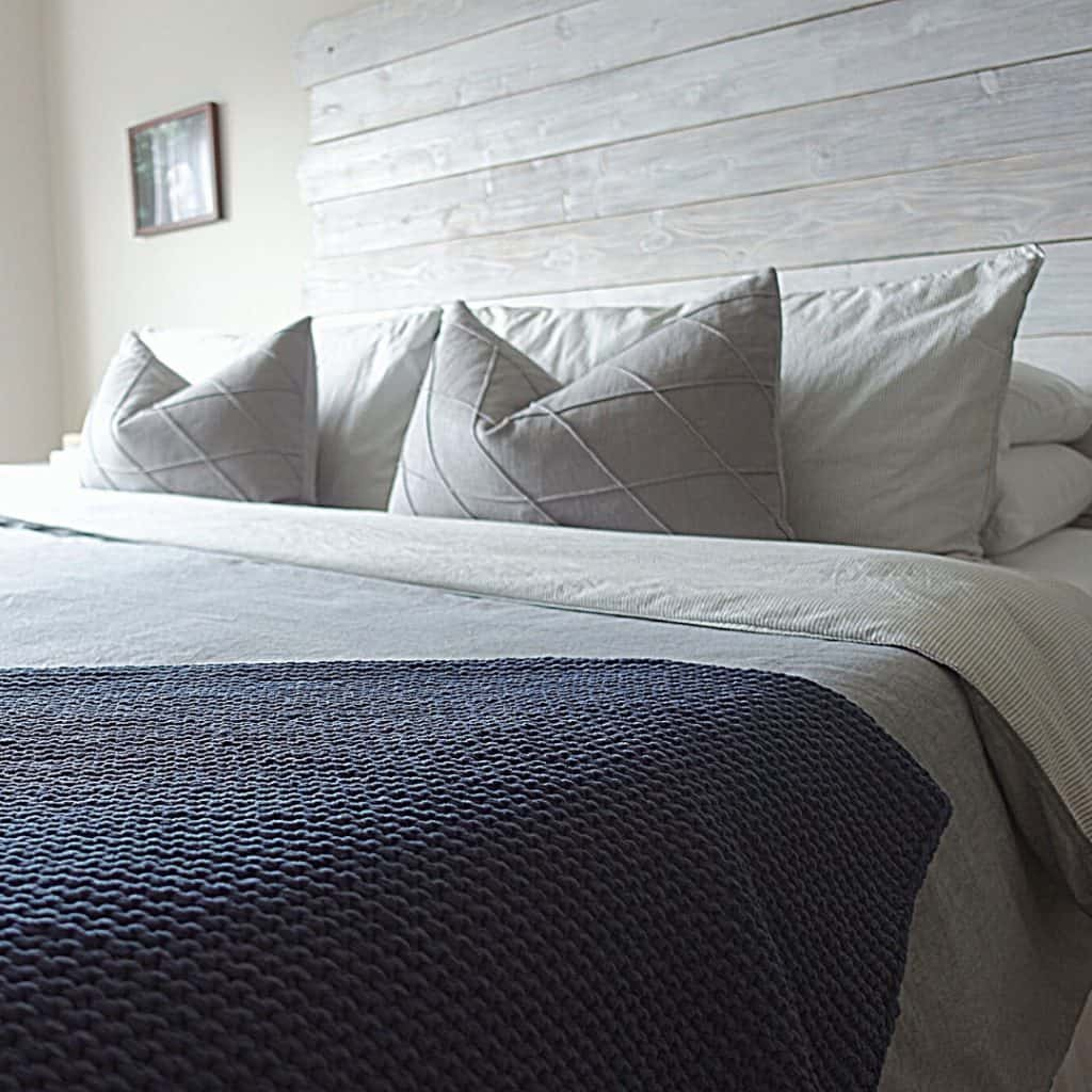 decluttering tips for hoarders image of a well made bed with karate chopped pillows and a blue blanket with grey comforter