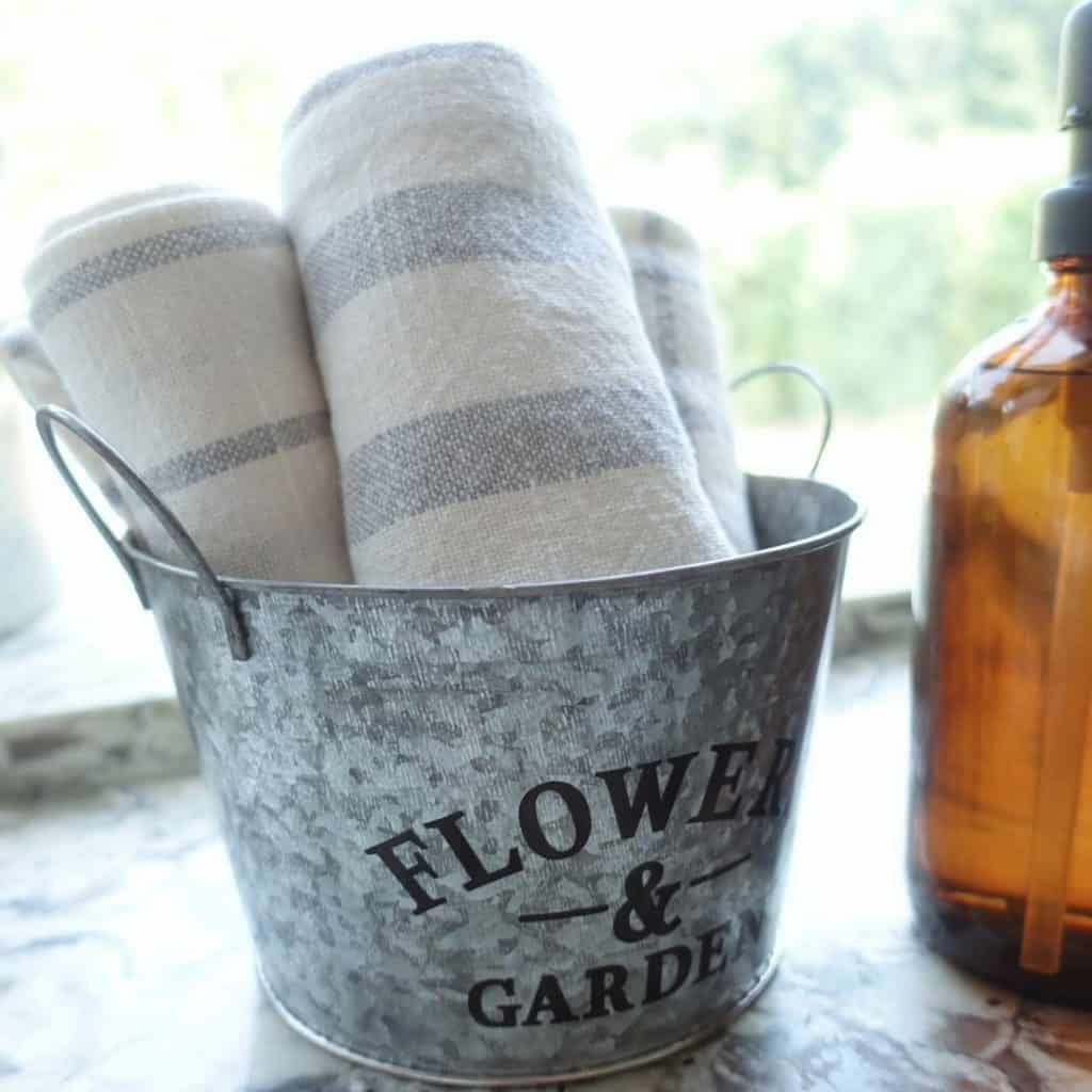 galvanized bucket from the dollar store storing striped tea towels sitting next to amber soap jars